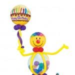 1,30m hohe Sulptur mit Smilyfolienkopf ,durchsichtigen Bauch der mit kleinen Ballons gefüllt ist, hält ein Bubble mit Kerzenaufdruck in der Hand